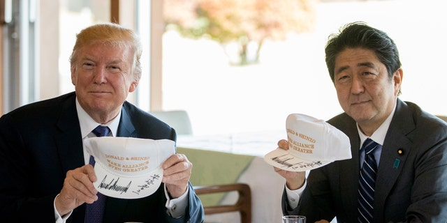 """U.S. President Donald Trump and Japan's Prime Minister Shinzo Abe display hats bearing the slogan, """"Donald and Shinzo: Make Alliance Even Greater."""""""