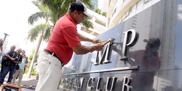 A worker removes the Trump name from the Trump Ocean Club International Hotel and Tower in Panama City, Panama March 5, 2018.
