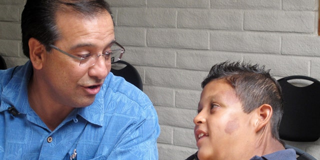"""In this July 20, 2012, photo, Si Budagher, the pastor of First Baptist Church of Rio Rancho, N.M. speaks with 9-year-old Juarez, Mexico-born boy suffering from massive tumor who U.S. Homeland Security identified only as """"Jose,"""" at the First Baptist Church of Rio Rancho, N.M. His family says U.S. federal agents sent in an armored vehicle earlier in the week to their dangerous Juarez neighborhood to help transport the boy and his parents to Albuquerque, N.M. so the boy could receive treatment. (AP Photo/Russell Contreras)"""