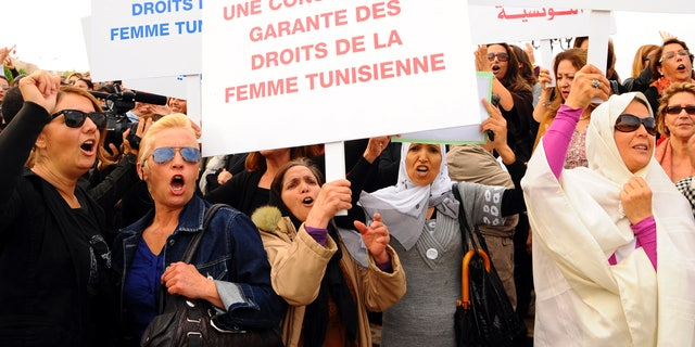 November 2: Tunisian women demonstrate for their rights during a protest in Tunis. Placards read in French: A constitution guaranteeing the rights of the Tunisian women.