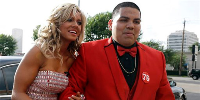 High school student Michael Ramirez, right, and Houston Texans cheerleader Caitlyn pose for pictures outside a restaurant before attending the prom Saturday, May 10, 2014, in Houston. Ramirez sent Caitlyn a Twitter message saying âIf I get 10,000 retweets will you go to prom with me (insert smiley face.) you will get asked in a cute way!â He did and so she said yes. (AP Photo/Pat Sullivan)
