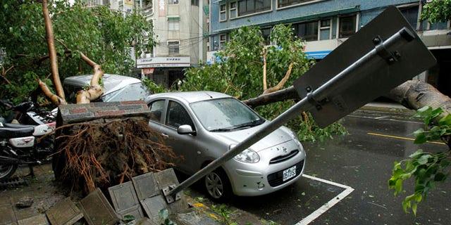 July 13, 2013: Fallen trees damaging vehicles lie on a street after Typhoon Soulik hit Taiwan in Taipei.