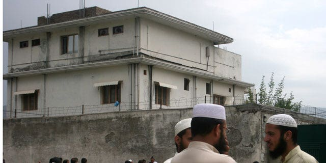 In this May 5, 2011 file photo, local residents and media are seen outside the house where Al Qaeda leader Usama bin Laden was caught and killed in Abbottabad, Pakistan.