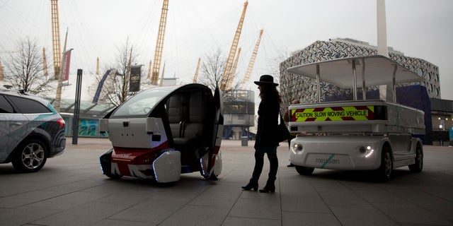 A woman poses for photographers beside a prototype driverless car called a LUTZ Pathfinder Pod, center, and a Meridian shuttle, right, during a launch event for the media near the O2 Arena in London.