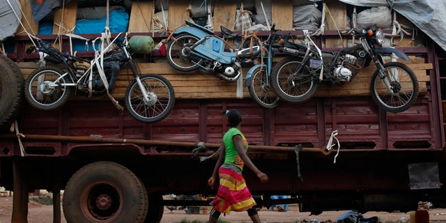 April 9, 2014: A woman walks past a truck waiting to leave for Chad loaded with goods belonging to Muslim residents of the PK5 district of Bangui, Central African Republic.