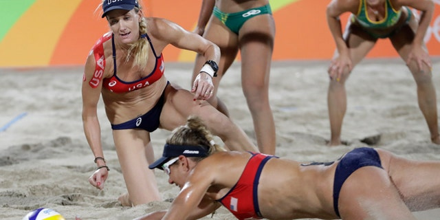 United States' Kerri Walsh Jennings, left, watches her teammate April Ross, right, trying to reach a ball during a women's beach volleyball semifinal match against Brazil at the 2016 Summer Olympics in Rio de Janeiro, Brazil, Wednesday, Aug. 17, 2016. (AP Photo/Petr David Josek)