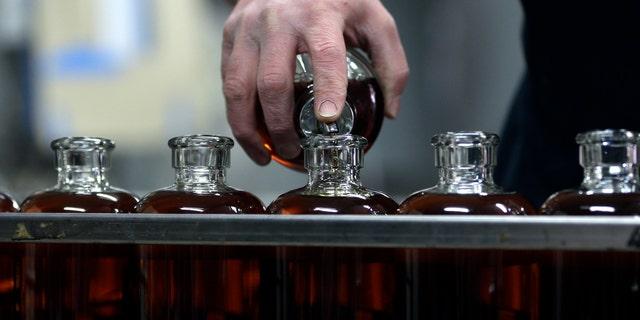 Distilleryman Brian Messina tops off bottles of baby bourbon on the bottling line at Tuthilltown Spirits.