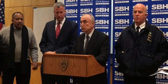 New York City Mayor Bill de Blasio, second left, stands by as Police Commissioner William Bratton, second right,speaks at a news conference at St. Barnabas Hospital in the Bronx section of New York City after two New York City police officers were shot. The two officers responding to a robbery in the Bronx were shot and wounded Monday night, and a manhunt was underway for at least two suspects, authorities said. The officers were taken to the hospital with non-life threatening injuries. (AP Photo/Tom McElroy)