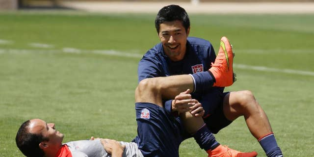 United States forward Landon Donovan stretches with assistance from a trainer in preparation for the World Cup soccer tournament on Thursday, May 22, 2014, in Stanford, Calif. (AP Photo/Ben Margot)