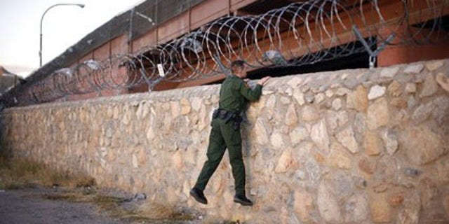 A United States Border Patrol agent checks an area under a bridge crossing between the United States and Mexico in El Paso, Texas November 14, 2010.  El Paso lies across the border from Ciudad Juarez, Mexico, a violent city on the frontlines of Mexico's war against drug cartels. Picture taken November 14, 2010.