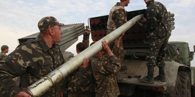 Aug. 18, 2014: Ukrainian soldiers load a Grad missile during fighting with pro-Russian separatists close to Luhansk, eastern Ukraine.