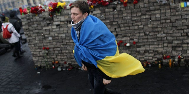 February 23, 2014: A youth draped in Ukraine's flag passes by a memorial to protesters killed in clashes with the police at Independence Square in Kiev, Ukraine. (AP Photo/ Marko Drobnjakovic)