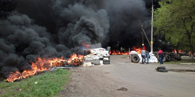 April 24, 2014: Black smoke billows from burning tires at a checkpoint following an attack by Ukrainian troops outside Slovyansk, Ukraine.