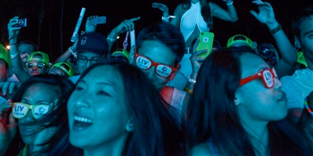 IMAGE DISTRIBUTED FOR NEON SPORT - The crowd dances to the music during Miami Reboot party which kicked off Ultra, the Electronic Music Dance festival during Miami Music Week on Thursday March 27, 2014 in South Beach, Miami. Attended by over 2,000 people, Miami Reboot was sponsored by Protocol Recordings and Neon Sport, sports nutrition drink from Cellucor. (Josh Ritchie/AP Images for Neon Sport)