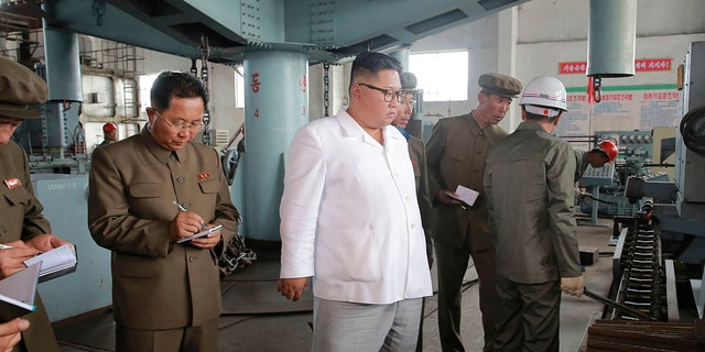 North Korean leader Kim Jong Un, center, speaks during a visit to a machine factory in North Hamgyong Province, North Korea.
