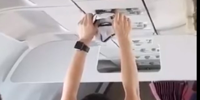 A woman on a flight from Turfy to Russia was caught on video drying a pair of underwear with the overhead vent.