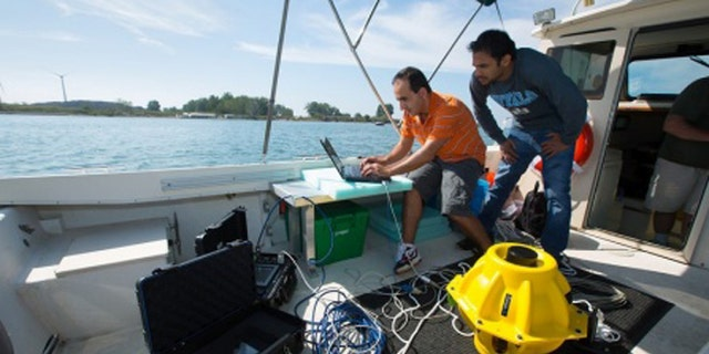 """Doctoral candidates with the University of Buffalo drop two 40-pound sensors into the water to test out an """"underwater Internet"""" using sonar rather than radio waves."""