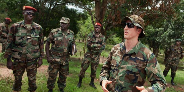 U.S. Army special forces Captain Gregory, 29, from Texas, right, who would only give his first name in accordance with special forces security guidelines, speaks in 2012 with troops from the Central African Republic and Uganda who are searching for Joseph Kony's Lord's Resistance Army (LRA), in Obo, Central African Republic. The Obama administration said in January 2015 that it has taken into custody a man claiming to be Dominic Ongwen, a top member of Joseph Kony's Lord's Resistance Army who is wanted by the International Criminal Court, after the man surrendered to U.S. forces in the Central African Republic. (AP Photo/Ben Curtis, File)