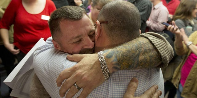 Dec. 20, 2013 file photo, Chris Serrano, left, and Clifton Webb embrace after being married, at the marriage division of the Salt Lake County Clerk's Office in Salt Lake City.