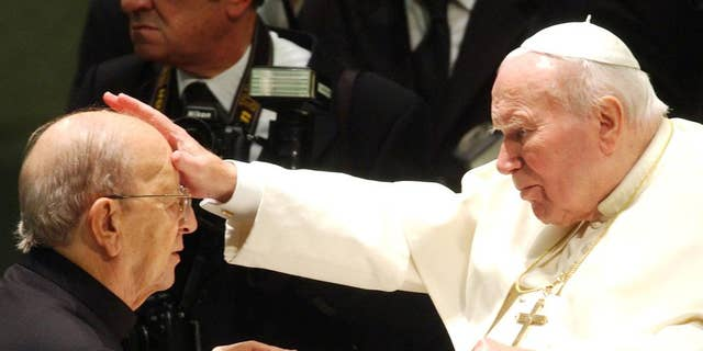 FILE - In this Nov. 30, 2004 file photo,  Pope John Paul II gives his blessing to late father Marcial Maciel, founder of Christ's Legionaries, during a special audience the pontiff granted to about four thousand participants of the Regnum Christi movement, at the Vatican. Pope John Paul II is rightly credited with having helped bring down communism, of inspiring a new generation of Catholics with a globe-trotting papacy and of explaining church teaching on a range of hot-button issues as Christianity entered its third millennium. But the sexual abuse scandal that festered under his watch remains a stain on his legacy. John Paul and his top advisers failed to grasp the severity of the abuse problem until very late in his 26-year papacy, even though U.S. bishops had been petitioning the Holy See since the late-1980s for a faster way to defrock pedophile priests. (AP Photo/Plinio Lepri, File)