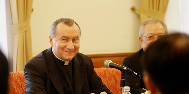 FILE - In this Feb. 16, 2009 file photo Monsignor Pietro Parolin, center, smiles during a meeting in Hanoi, Vietnam. The Vatican announced Saturday, Aug. 31, 2013 that the Italian archbishop, Pietro Parolin, 58, will take up the post held since 2006 by Italian Cardinal Tarcisio Bertone, starting Oct. 15. Pope Francis has tapped a veteran Vatican diplomat to replace the Holy Seeâs secretary of state who in recent years increasingly became a divisive figure in the Catholic churchâs hierarchy. (AP Photo/Chitose Suzuki, file)
