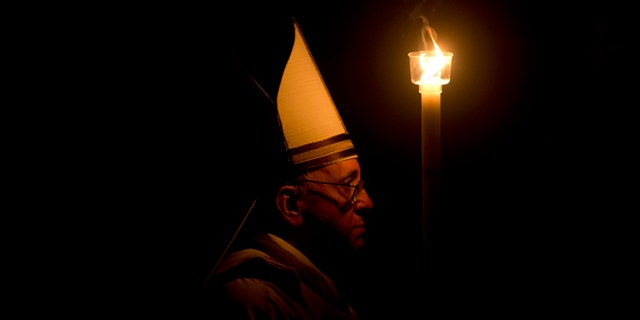 March 30, 2013: Pope Francis holding a tall, lit, white candle, enters a darkened St. Peter's Basilica, at the Vatican to begin the Vatican's Easter vigil service.
