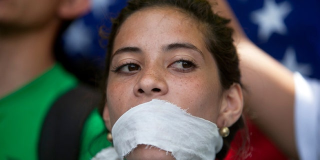 A demonstrator covers her mouth with a rag to prostest government censorship, during a march to Venezuelan Telecommunications Regulator Office or CONATEL in Caracas, Venezuela, Monday, Feb17, 2014. Students, whoâve spent the past week on the streets alternating between peaceful protests by day and battles with police at night, marched on Monday to Venezuelaâs telecom regulator to demand it lift all restrictions on the mediaâs coverage of the unfolding political crisis. (AP Photo/Alejandro Cegarra)