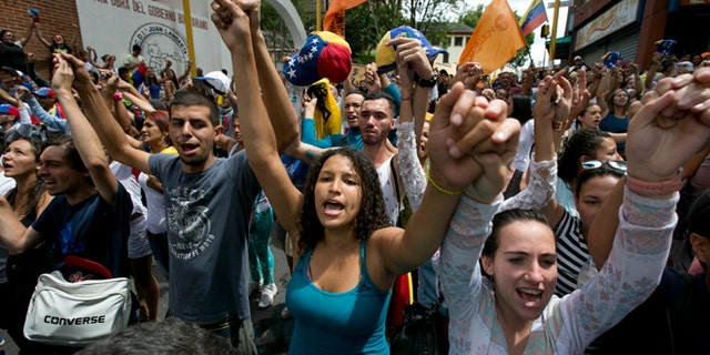 FILE - In this Sept. 7, 2016, file photo, demonstrators sing Venezuela's national anthem during a protest against the government of Venezuela's President Nicolas Maduro in Los Teques on the outskirts of Caracas, Venezuela. As the country's economy has only gone further into its tailspin the Venezuelan professional class that makes up the bedrock of the oppositions support is eager to see President Nicolas Maduro go. (AP Photo/Ariana Cubillos, File)