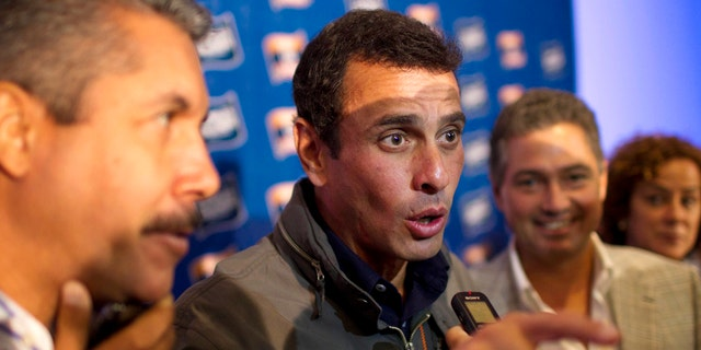 Opposition leader Henrique Capriles, center, speaks to the press. (AP Photo/Ariana Cubillos)