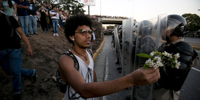 A student offers a small bouquet of flowers to police officers during a protest in Caracas, Venezuela, Friday, Feb. 14, 2014. Students are protesting the Wednesday killings of two university students who were shot in different incidents following an anti-government protest that demanded the release of student protesters who had been arrested in various parts of the country.(AP Photo/Alejandro Cegarra)