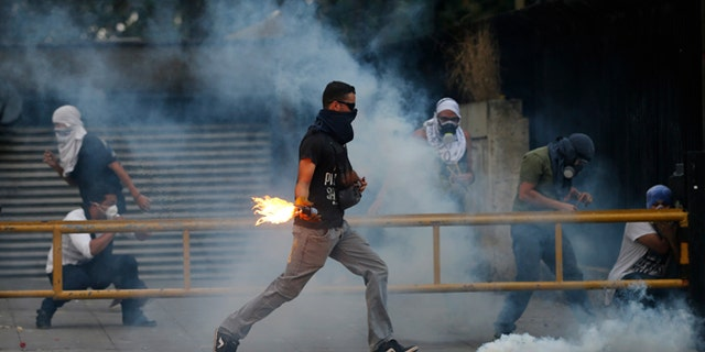 A demonstrator runs to throw a molotov bomb against Bolivarian National Police officers during clashes in Caracas, Venezuela, Thursday, March 6, 2014. A National Guardsman and a civilian were killed Thursday in a clash between residents of a Caracas neighborhood and armed men who tried to remove a barricade, Venezuelan officials said. (AP Photo/Fernando Llano)