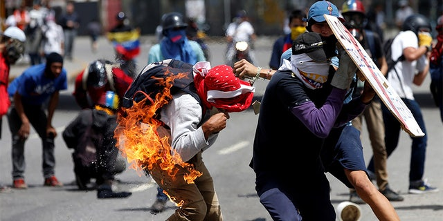 A demonstrator sets himself on fire when he tries to hurl a molotov cocktail during a protest against Venezuela's president.