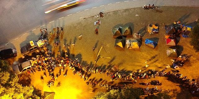 Venezuelans line up behind a vehicle providing free meals