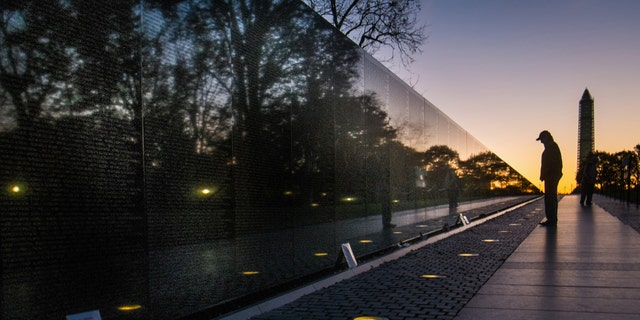 A visitor at the Vietnam War Memorial in Washington passes early in the morning on Veterans Day, Monday, to look at the names inscribed on the wall.