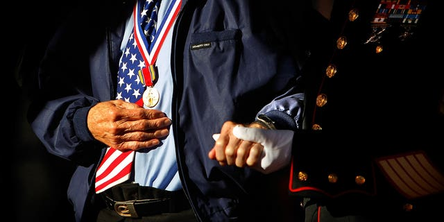 Marine Corps veteran Jim Brown, 83, (right) who served in Vietnam and Korea helps D-Day Veteran Howard Mills, 91, to the stage for special recognition during a Veteran's Day ceremony in Collierville, Tenn. Sunday, Nov. 10, 2013. (AP Photo/The Commercial Appeal, Jim Weber)
