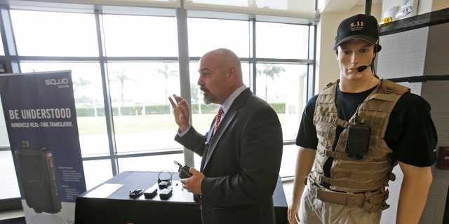 John Hall, president and CEO of Voxtec International, demonstrates his company's real-time translation system, during a media opportunity at the U.S. Southern Command headquarters.