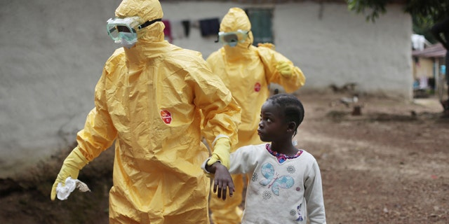 FILE - In this Tuesday, Sept. 30, 2014 file photo, Nowa Paye, 9, is taken to an ambulance after showing signs of Ebola infection in the village of Freeman Reserve, about 30 miles north of Monrovia, in Liberia. (AP Photo/Jerome Delay, File)
