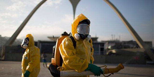 FILE - In this Tuesday, Jan. 26, 2016 file photo, a health workers stands in the Sambadrome spraying insecticide to combat the Aedes aegypti mosquito that transmits the Zika virus in Rio de Janeiro, Brazil. The Sambadrome will be used for the Archery competition during the 2016 summer games. With the opening ceremony less than three months away, a Canadian professor has called for the Rio Olympics to be postponed or moved because of the Zika outbreak, warning the influx of visitors to Brazil will result in the avoidable birth of malformed babies. The IOC and World Health Organization disagree, saying Zika will not derail the games.   (AP Photo/Leo Correa, File)