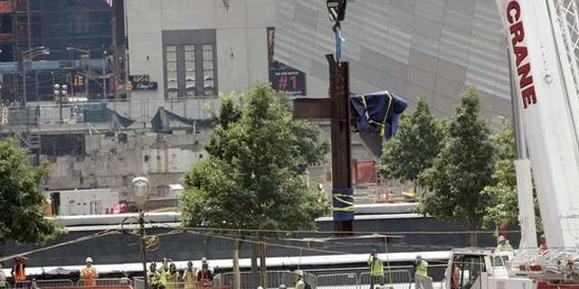 July 23: The World Trade Center Cross, made of intersecting steel beams found in the rubble of buildings destroyed in the September 11 attacks on the World Trade Center, is raised by a crane before being transported and lowered into an opening in the World Trade Center site below ground level where it will become part of the permanent installation exhibit in the 9/11 Memorial and Museum.