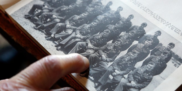 May 8, 2014: World War II veteran Arthur Robinson of Saratoga Springs, N.Y., points to himself in a 1940 photograph with his unit at the New York State Military Museum in Saratoga Springs. (AP)