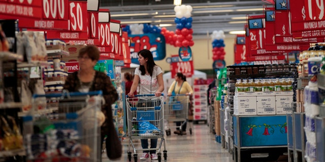In this Sept. 1, 2015, photo, women shop in a Wal-Mart Lider hypermarket in Santiago, Chile. Soon after Wal-Mart's acquisition of the countrys largest supermarket chain Distribucion y Servicio, S.A., Wal-Mart made red the signature color for price signs for its Lider supercenters because Chileans associate red with good deals. (AP Photo/Luis Hidalgo)