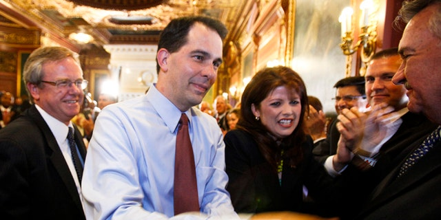 June 6, 2012: Wisconsin Gov. Scott Walker, second from left, and Lt. Gov. Rebecca Kleefisch are greeted by the governor's cabinet and staff at the Wisconsin State Capitol in Madison.