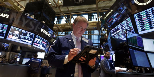 In this  file photo, Trader F. Hill Creekmore works on the floor of the New York Stock Exchange.