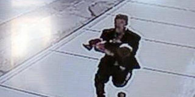 FILE - In this still image taken from surveillance video on March 8, 2015, and provided by the Lincoln County Sheriff's Office, a man runs down a street, carrying a toddler in an apparent kidnapping attempt in Sprague, Wash. A 15-year-old boy was arrested Wednesday in connection with the attempted kidnapping of a 22-month-old toddler that was caught on surveillance video. The teenage boy, who lives in Sprague, was identified through the use of surveillance video, interviews and evidence collection, Lincoln County Sheriff Wade Magers said. The boy's identity was being withheld because he is a juvenile, Magers said. (AP Photo/Lincoln County Sheriff's Office)