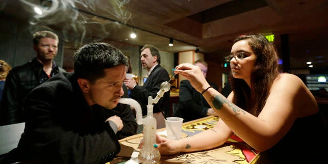 March 2, 2013: John Connelly, left, inhales marijuana vapor with the help of bar worker Jenae DeCampo, right, in the upstairs lounge area of Stonegate, a pizza-and-rum bar in Tacoma, Wash.