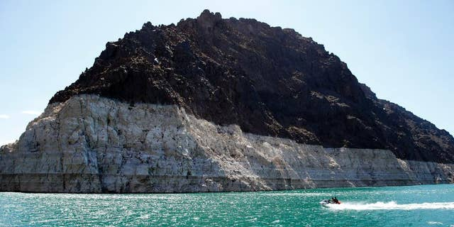 FILE - In this July 17, 2014 file photo, recreational boaters ride by a bathtub ring that delineates the high water mark at Lake Mead in the Lake Mead National Recreation Area in Nevada. Water managers in Las Vegas and the Los Angeles area have reached a deal to draw enough water to serve some 300,000 homes from the Lake Mead reservoir on the Colorado River and sell it to California. (AP Photo/John Locher,File)