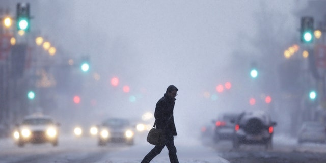 Jan. 21, 2014: A man crosses Broad Street during a winter snowstorm in Philadelphia.