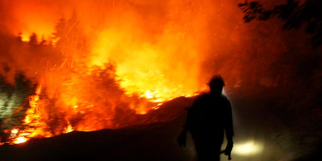 Aug 30, 2103: A firefighter uses a headlamp at the Rim Fire at night in this undated United States Forest Service handout photo near Yosemite National Park, California.