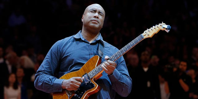 FILe - In this Feb. 1, 2014, file photo, former New York Yankee baseball player Bernie Williams plays the nation anthem on a guitar before an NBA basketball game between the Miami Heat and the New York Knicks, in New York. Williams stopped being a baseball player in 2006. Since age 7, he hasnât stopped being a musician. His father brought a guitar back from a trip to Spain while serving in the Merchant Marines, and Williams fell in love with music after learning the first few chords. (AP Photo/Jason DeCrow, File)