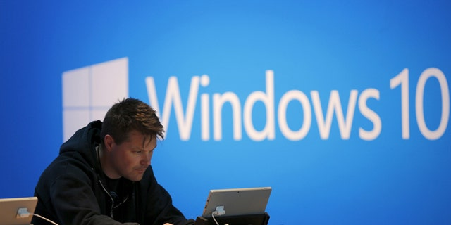 File photo - A man works on a laptop computer near a Windows 10 display at Microsoft Build in San Francisco, California April 29, 2015.